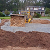10/13/09 - Tuesday<br /> <br /> The dump trucks full of builder's sand delivered load after load all day to the center of the site through the east wall. Phil uses the loader to dump the sand into the front porch, while his son smooths out the sand on the dog room porch.