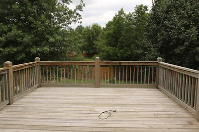 Looking east out the main level rear door across the wood deck.  Note the privacy inherent in the location & arrangement of adjacent homes.  The 16 x 16 wood deck provides a spacious venue for outdoor entertaining, and is fully shaded on summer evenings.