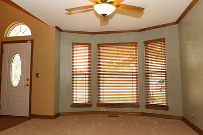 Formal Dining Room - looking toward bay windows on west wall.  Custom-made wood venetian blinds are featured on all windows throughout the home (with the exception of the window over the kitchen sink).