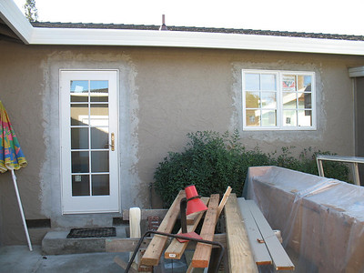 New kitchen door and window over the sink. The stucco has been patched and needs to be painted.