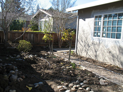 This will be our idyllic courtyard, laid with Connecticut bluestone and framed by whimsical flowers. The roses have been adopted by our neighbors.