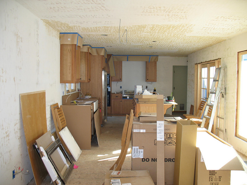 Messy view of the kitchen and dinning space from the living space of the great room.
