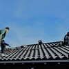02/07/17: Rob hauling up custom cut tiles to be put back in place. Duane (to the right) is sealing the mounting hardware to ensure the roof integrity remains waterproof.
