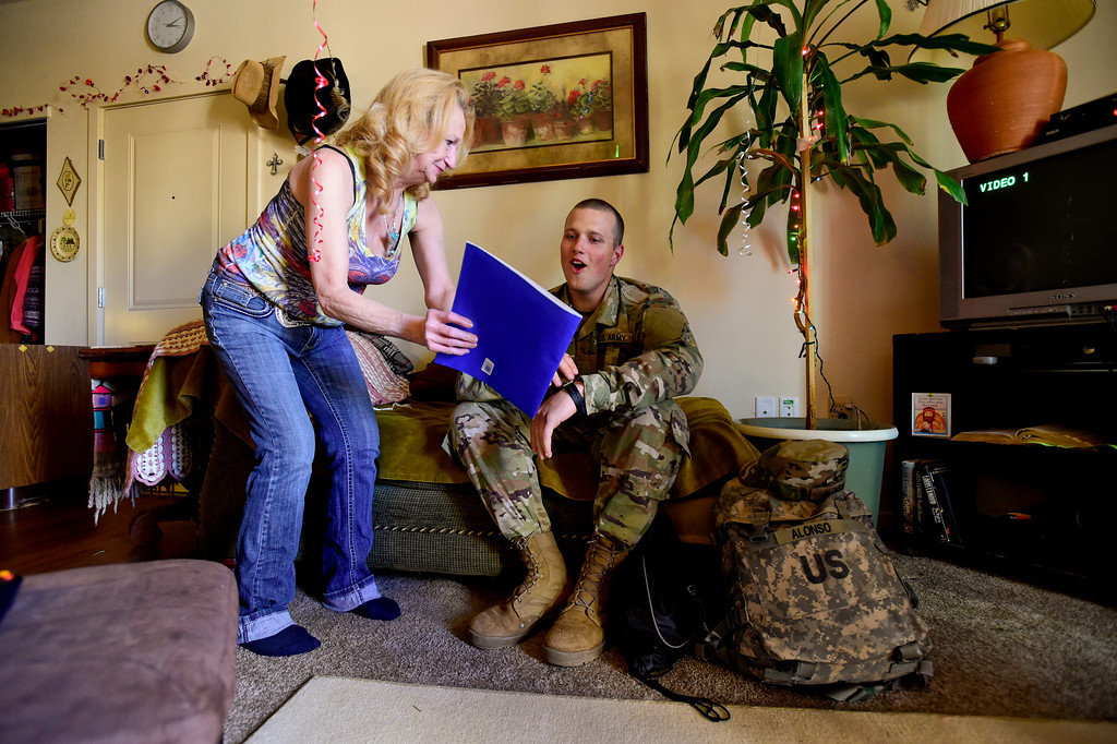 . Adam Alonso shares a laugh with his mother Teresa Alonso after she shows him a photo of him as a kid dressed in military fatigues in Longmont, Colorado on Dec. 19, 2017. (Photo by Matthew Jonas/Staff Photographer)