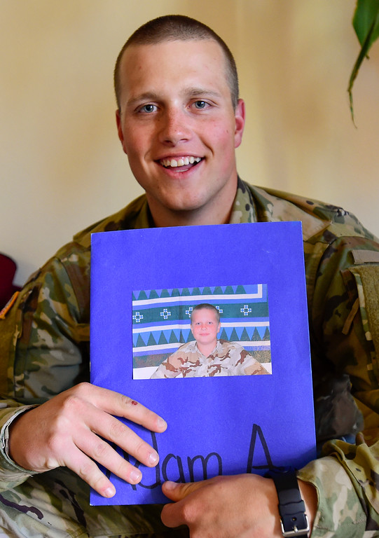 . Adam Alonso holds a photo of him as a kid wearing military fatigues in Longmont, Colorado on Dec. 19, 2017. (Photo by Matthew Jonas/Staff Photographer)