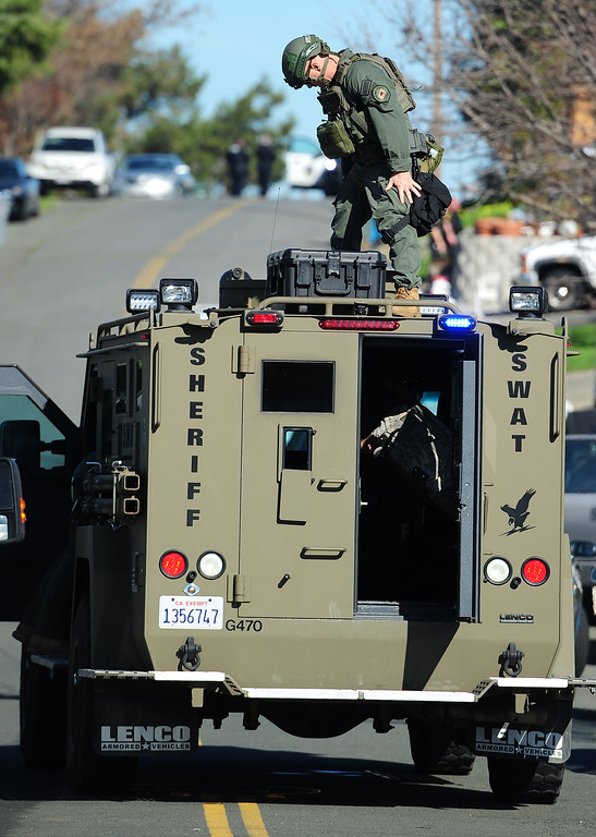 . (CHRIS RILEY �TIMES-HERALD) A Sheriff SWAT team member stands on top of an armored vehicle during the search for two homcide suspects on Thursday.