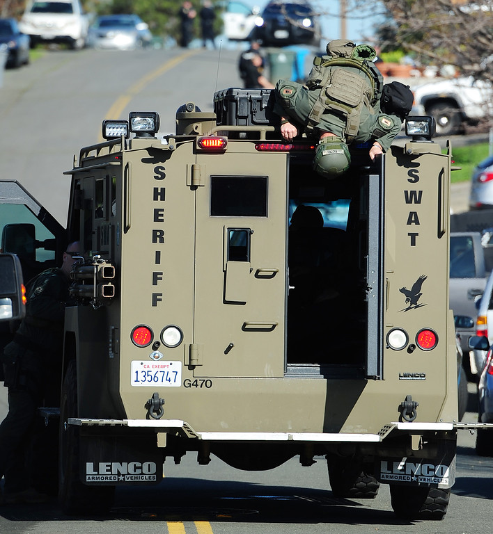 . (CHRIS RILEY �TIMES-HERALD) A Sheriff SWAT team member looks into the back of an armored vehicle during the search for two homcide suspects on Thursday.