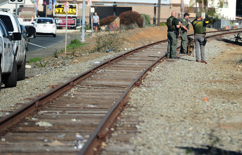. (CHRIS RILEY �TIMES-HERALD) Sheriff deputies keep an eye on the railroad tracks near Broadway as the search for two homcide suspects continued on Thursday.
