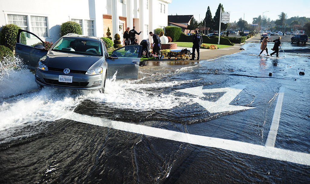 . (CHRIS RILEY �TIMES-HERALD) A woman is helped across a flooded Redwood Street after the vehicle she was in ended up on top of a fire hydrant after a crash with home invasion homicide suspects out of Santa Rosa.