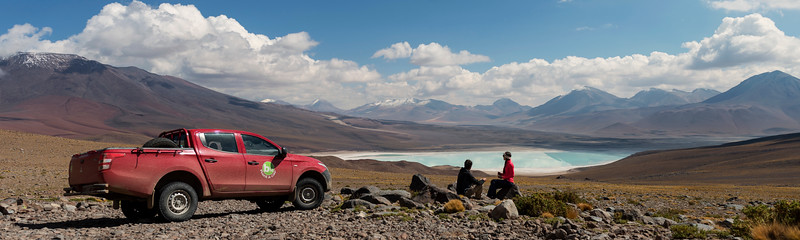 Young travellers on a 4x4 tour and camping in South America, enjoying the views at breakfast on Laguna Verde from the foot of Volcano Licancabur in Bolivia near the Chilean border