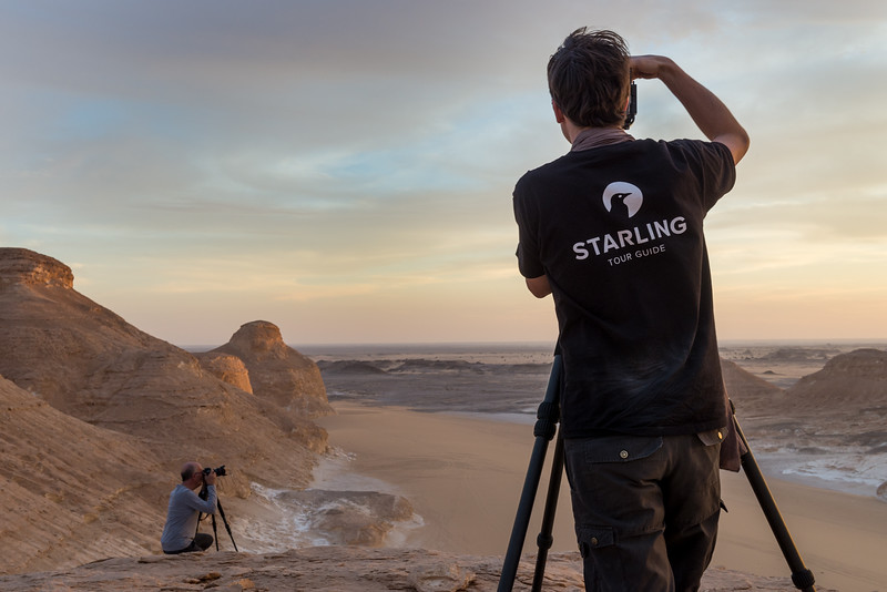 A photography guide tour and an amateur photographer take pictures in the White Desert, in Egypt at sunset.