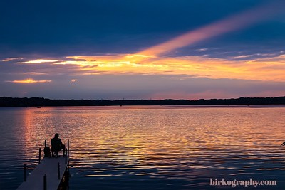 A fisherman sits on the dock as the sun sets on Medicine Lake, MN
