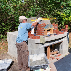 Doc buidls the brick arch for the pizza oven.