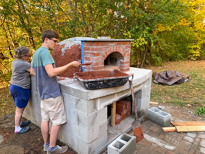 Spreading 'structural skin' over the dome of the pizza oven.