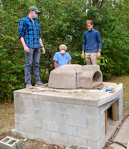 Billy, Doc, and Andy celebrate the assembly of the concrete dome for the pizza oven.