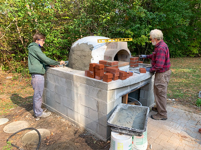 Andy spreads mortar over the insulation layer on the pizza oven while Doc begins work on the brick facade.
