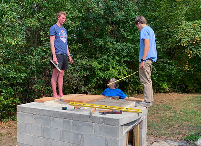 Billy and Andy lay out the base for the pizza oven.