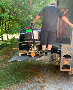 The truck driver delivers the pizza-oven kit.