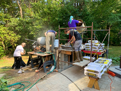 Pam, Doc, Andy, and Mara working to pour the concrete base for the pizza oven.