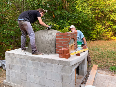 Spreading mortar over the insulation layer on the pizza oven.