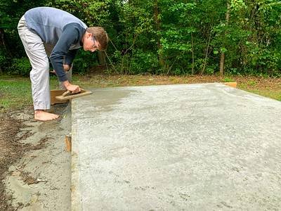 Andy does some finish troweling on the footer for the pizza oven.