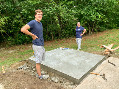 Andy and Pam unbox the concrete footer for the pizza-oven base.