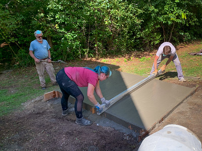 Doc shows Mara and Andy how to screed the concrete for the footer of the pizza oven.