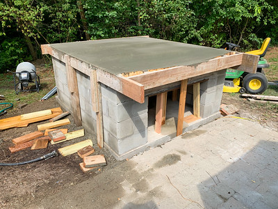The concrete has been poured, forming the base for the pizza oven.
