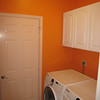 Cabinet doors painted white semi-gloss to complement the washer/dryer and shelves opposite.