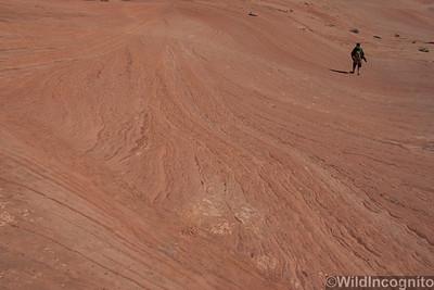 Hiker descends the slick rock towards The Subway Zion National Park