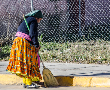 Tarahumara lady sweeps the streets. They all dress in colourful skirts and shawls.