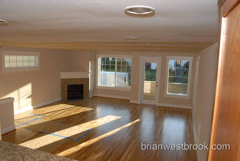 Here's the amazing living room shot from the kitchen.  The front of the house is out the windows ahead.  As you can see, there's plenty of room for big-screen plasmas and comfy furniture.  Shopping spree!!
