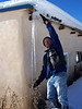 Chris displays a super-long icicle on the side of the adobe on New Year's Day.