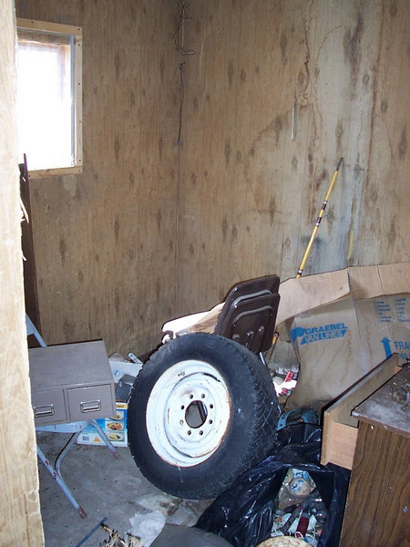 Pre-renovations: Inside the shed. This will be emptied and cleaned but the funky old wall covering will remain (It's just a shed!). We will scavenge through the junk and keep anything useful. Everything else will go to the dump.