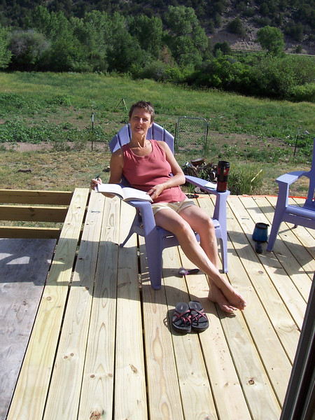 The deck is only two-thirds done but Caroline can't wait to use it. The boards underneath her aren't screwed down yet.