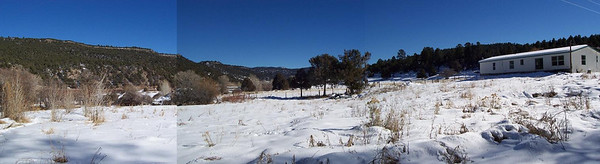 A panoramic view of the back yard and back of the mobile home.