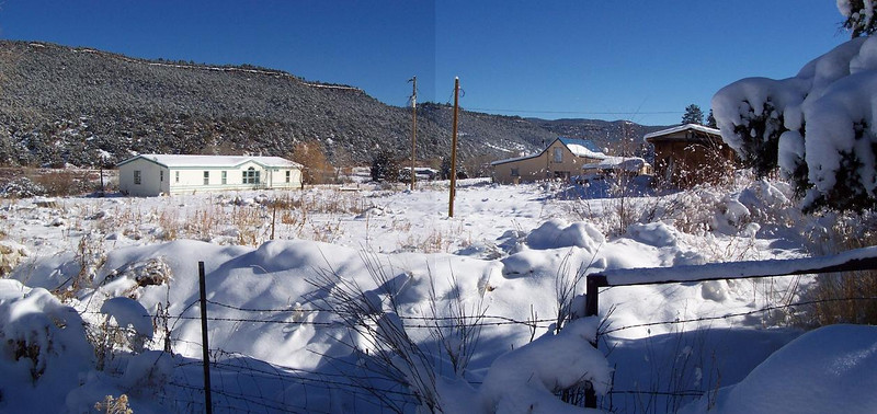 Panoramic photo shows the snow convering the mobile home, adobe, and shed on the Vadito property in December of 2007.