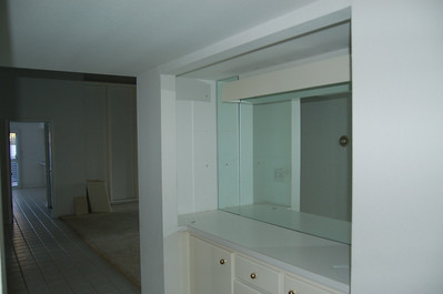 There was this dry  bar, with mirror, in the hallway. It's now a bookcase. We limited the depth of this space, used it in the master bedroom, and had a natural wood bookcase built into this nook.