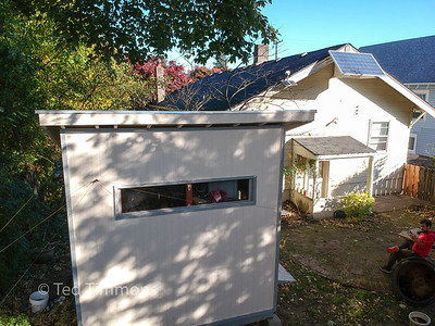 Shed and solar panel. The wires in the foreground are amateur radio antennas.