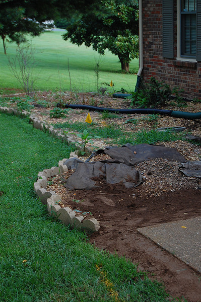 concrete slab leveled and dirt re-graded to prevent water undermining