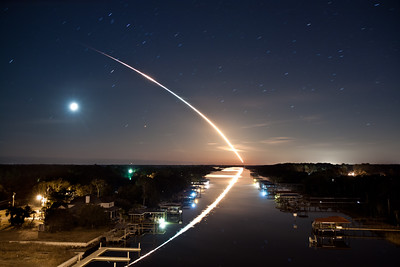 """02/08/2010 at 4:14 am - """"Waterway to Orbit"""" - Space Shuttle Endeavour STS-130 launches into orbit toward the east, as the stars and waning crescent moon trail toward the west, leaving a beautiful reflection on the Intracoastal Waterway in Ponte Vedra, Florida. This 132-second time exposure of the final night launch of a Space Shuttle, from launch through SRB separation, was taken 115 miles north of Launch Pad 39A at Kennedy Space Center.  The response to this photo has been absolutely amazing, so I've given it it's own gallery.  The photo has generally become known as """"Waterway to Orbit"""", thanks to Jerry Bonnell of the NASA Astronomy Picture of the Day.  I wanted to use this space to answer a few questions that have been emailed to me and that I have seen on the web.  (I admit it, I googled myself :D ).  If you have further questions or comments, or if you would like to be added to my mailing list, please feel free to  email me or leave a comment on this page.  What type of camera did you use and what were your settings for this picture? I used a Canon EOS Rebel T1i , with a Canon EF-S 17-55mm f/2.8 IS USM Lens   attached; no filters. I was pretty sure I had it set to 17mm but exif shows 18mm.  Maybe it creeped a bit while I was rushing to decide the exposure and composition.  Exposure was ISO 100, f/4, and 132 seconds.  Please let me know when I can purchase a copy. Hope it is soon. The photo is finally available for purchase!  Click the """"Buy"""" button at the top of this page to purchase a copy.  I priced them reasonably so as not to exclude anyone who is interested in purchasing.  Thanks so much for all of your interest and patience.  I am truly humbled.  Are you interested in licensing it for commercial projects? Absolutely.  Please  contact me if you are interested.  Have you altered the photo in any way?  Also how much post-production editing did you do to adjust the colors, etc. I did not alter the content of the image at all.  Really the only thing I did was so"""