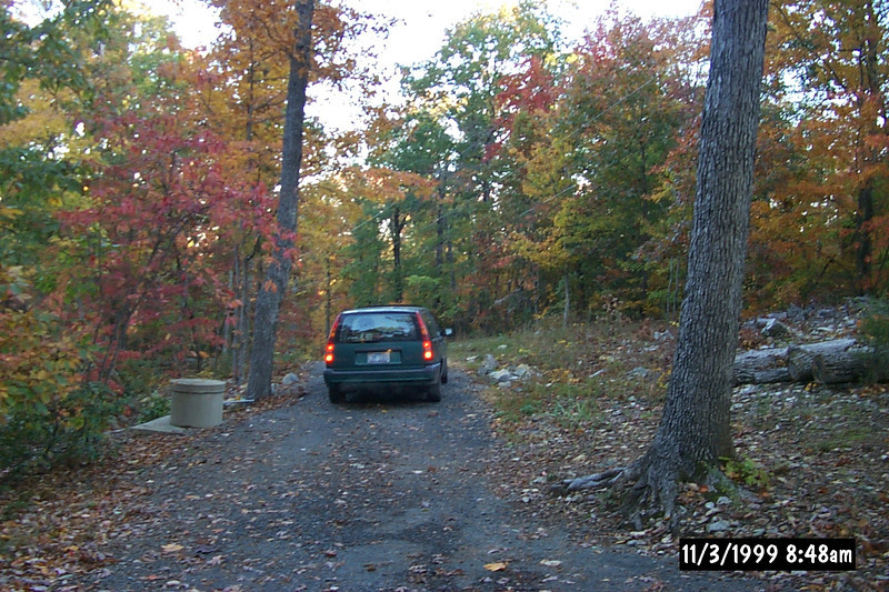 Here is our driveway before the garage and before any rocks were moved.<br /> Remember where the wellcap is located.  The garage will be down to the left with the lower<br /> driveway.  The wellcap will eventually have a rock wall built around it.  The 330 foot rock wall<br /> will be on the right with the curve up the powerline will be just beyond that big oak tree.