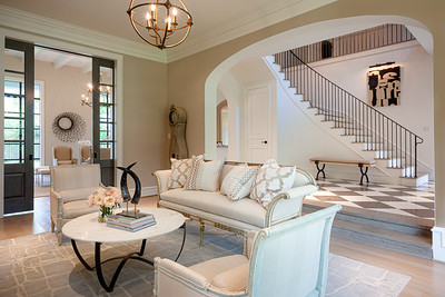 Beautiful formal living room, cream sofa and two matching side chairs, cream colored pillows with darker print accents. checkered entryway floor with curved staircase