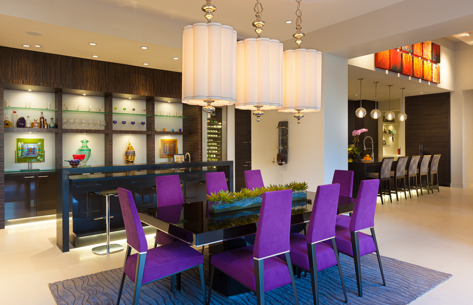 Colorful Dining Room with fuchsia colored dining chairs with 3 barrel pendants over the table.
