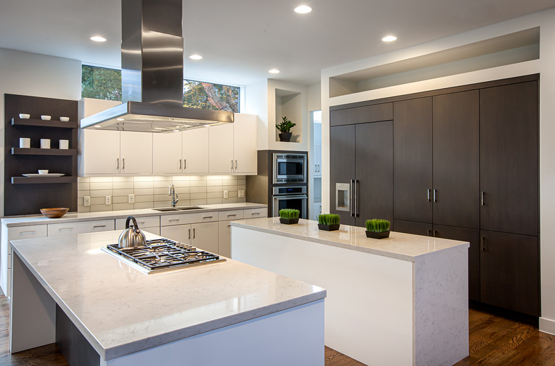 Modern Kitchen Interior with double island and beautiful wood covered refrigerator and cabinetry.