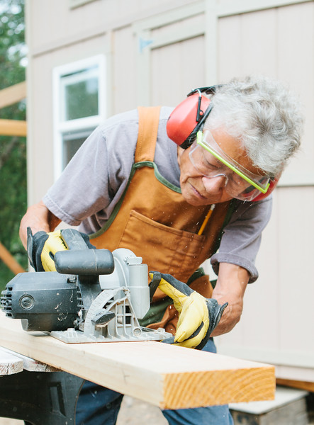 Elderly woman building a wooden shed using her carpentry skills