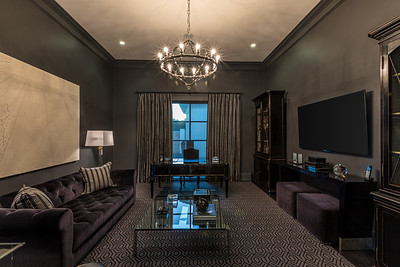 Dark media room with purple velvet sofa and purple velvet ottomans.