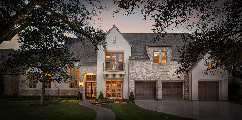 twilight photography architectural beautiful 3 car garage home with stone elements on the exterior