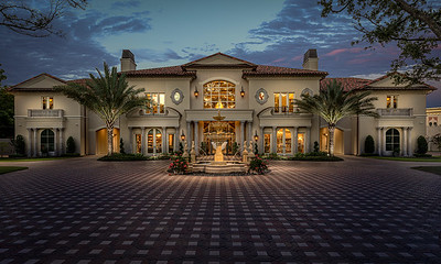 Mansion twilight, 2 palm trees and shrubs. water fountain in the middle of tiled drive.