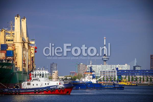 Sleepboten halen een zeeschip los van de kade in de haven van Rotterdam